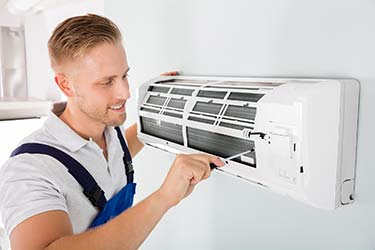 Smiling young technician performs maintenance and repairs on indoor HVAC unit