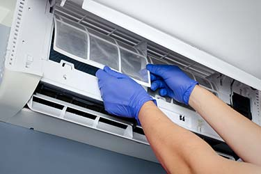 Professional air conditioner technician removes filter from indoor HVAC unit to clean for optimum performance