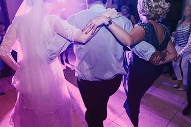 Family of the bride dance with guests to music played by DJ at wedding