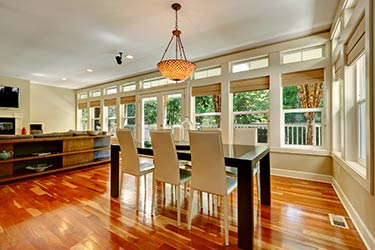 Minimalist dining room and lounge with bright, warm, quality hardwood flooring