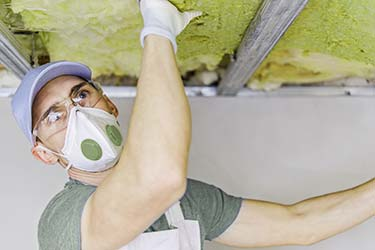 Tradesperson installing eco friendly insulation in roof of home
