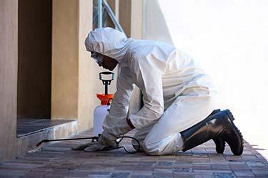Pest extermination technician in hazmat suit applying pest control treatments to property
