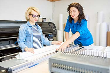 Printing company worker cutting printing supplies with customer in large format print shop