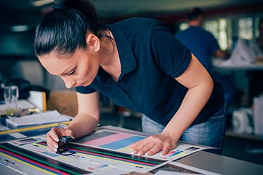 Print shop professional inspects colour integrity on wide format prints