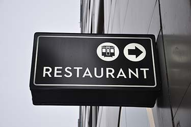 Minimalist signage for restaurant, including directions to nearby public transport
