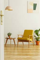 Professionally upholstered retro occasional chair in mustard colored cloth on wooden floor in light and modern living space