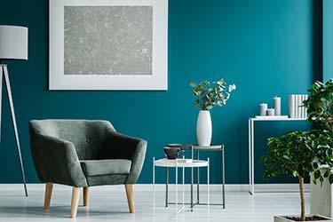 Designer lounge chair upholstered in forest green velvet in botanical themed living room