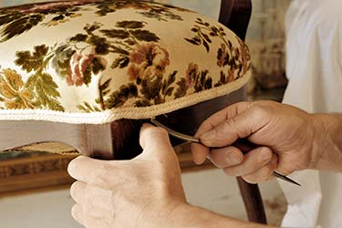 Upholsterer works skilfully on antique furniture to prepare for replacement of chair fabric